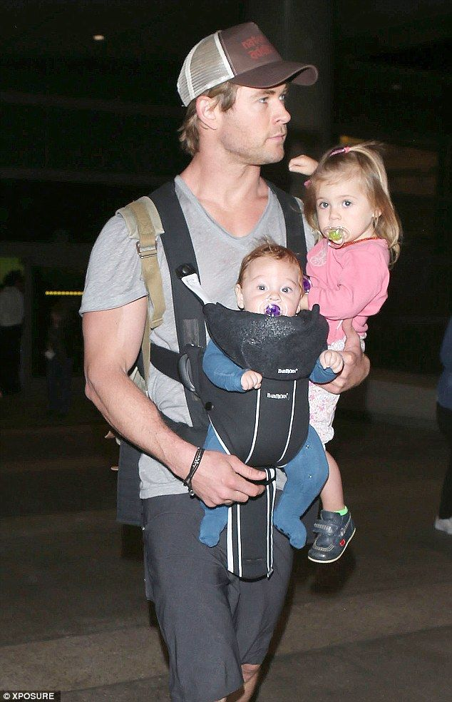 Daddy cool: Chris Hemsworth arrives at Los Angeles International Airport with some very important luggage