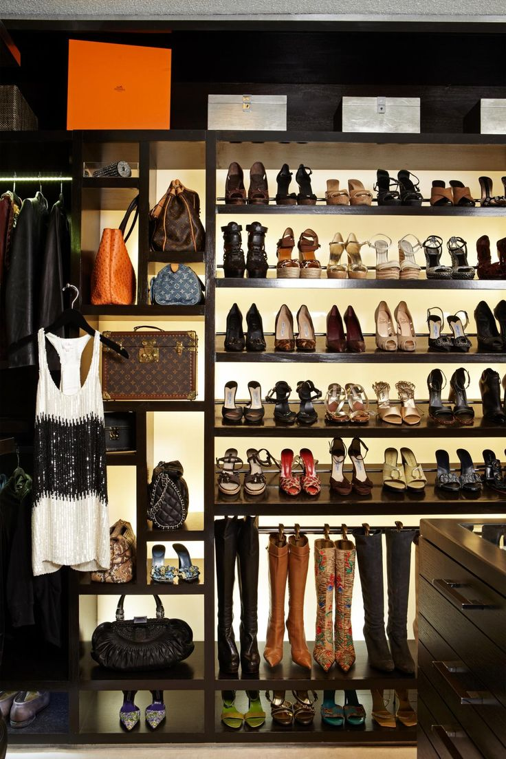 a custom shelving unit is the standout feature in this walkin closet stocked with bags and shoes the backlit shelves show off the sartorial goods while