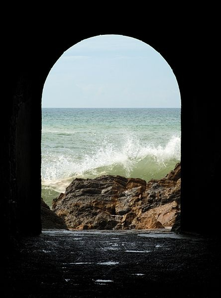 The tunnel of São Martinho do Porto, Portugal. Author: Alvesgaspar.  This file is licensed under the Creative Commons Attribution-Share Alike 3.0 Unported license: http://creativecommons.org/licenses/by-sa/3.0/deed.en #tunnel #entrance #sea #wave #stone #rock #sky