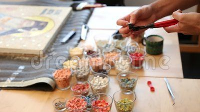Mosaic iconographer - breaks with a special tool pieces of colored stones.