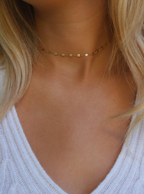 A dainty, elegant chain choker with lots of sparkle! Wear it as a choker or a short layering necklace! The shimmery chain is 14k gold filled. MEASURING YOUR SIZE:  1. Take a piece of string that can wrap around your neck 2. Wrap it around your neck exactly where you want your choker to sit 3. Using a ruler measure your string 4. Order the length that your string measures in inches (Example: If your neck measures 12.75, order the 13–14 size) (Example: If your neck measures 14.5, order the…