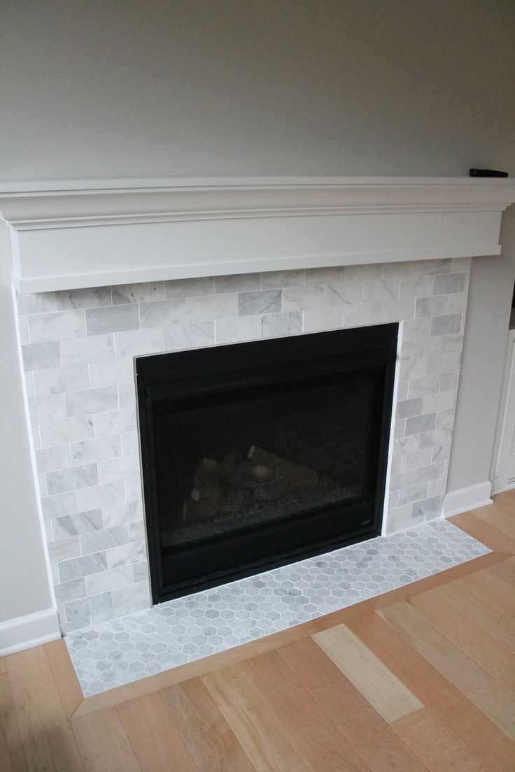 Marble tiles are a common way to add beauty to fireplaces. White is always a marketable and classic color. It is a bright color that reflects light and cleanliness. And marble is an ideal material for low traffic areas like fireplace surrounds. So this tile was a perfect choice!