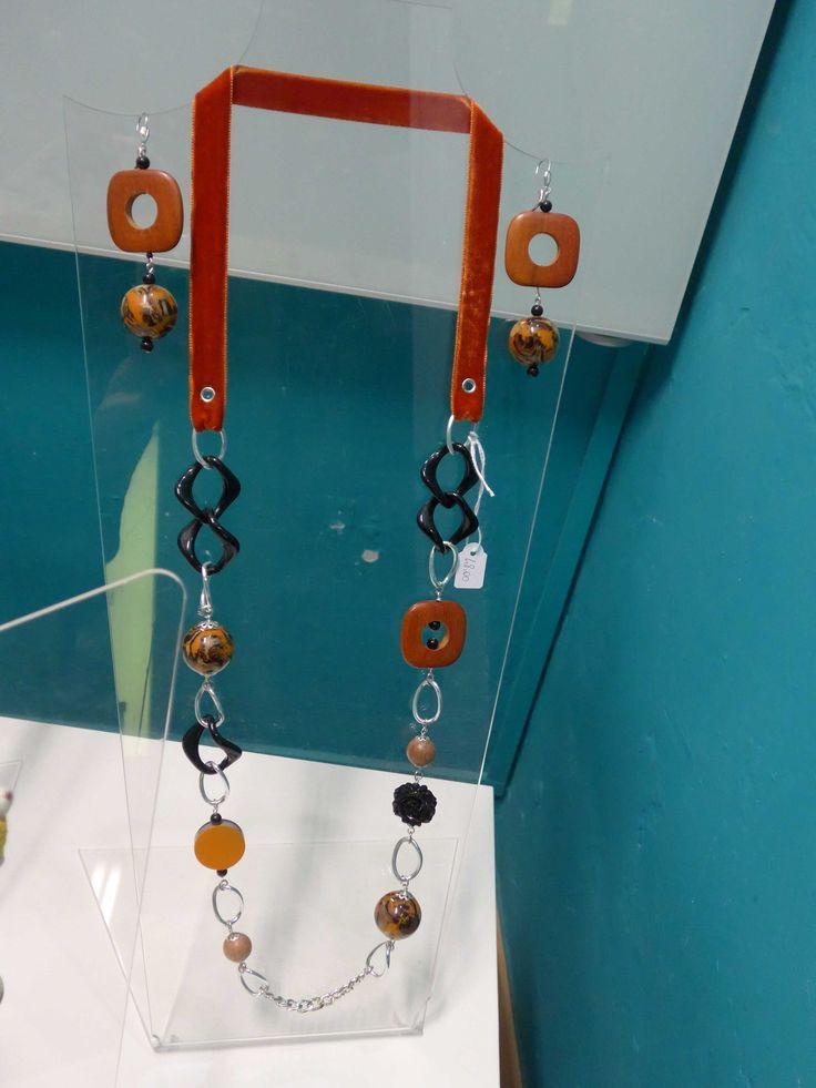 Collana realizzata con nastro di velluto bifaccia arancio, resine, legno e catena. Orecchini in resina e legno.