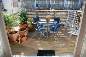 Floor-to-ceiling glass doors lead through to the large west-facing deck which catches the afternoon and evening sun. An outdoor dining set is provided Easter to October, as are large potted plants to provide lush greenery and a modicum of privacy. On the patio  below is a cold water shower to rinse off the sand after a hard day on the beach.