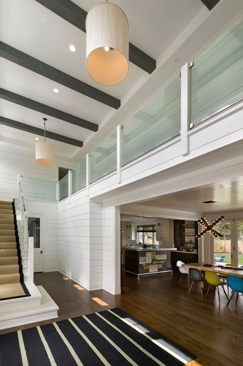 Two Story Foyer Features Gray Beams On Ceiling Dotted With Pot Lighting And  Linen Drum Light Pendants Over A Glass Stair Railing And Staircase Lined In  A ...
