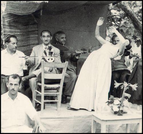 Ο Δημήτρης Πατρέλης, όρθιος δίπλα στον λυράρη, σε καφενείο που είχε ανοίξει κοντά στην παραλία του 'Αγίου Ισίδωρου, στο Πλωμάρι