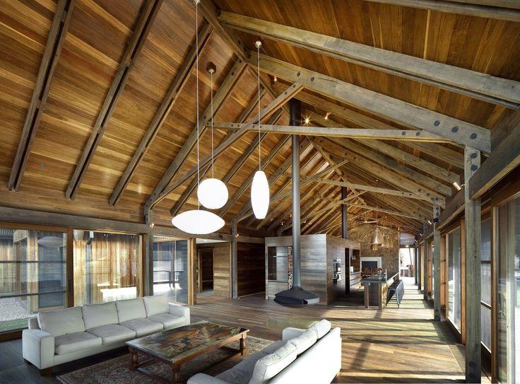 Modernas vigas de madera en tono gris, soportando un techo a dos aguas.