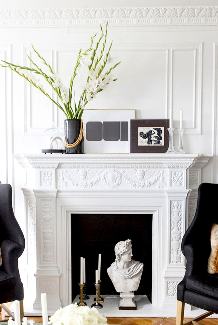 White fireplace mantel styled with artwork and a tall flower arrangement