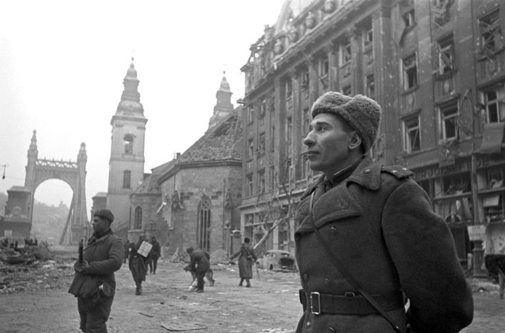 Soviet soldiers are photographed in front of the Elisabeth Bridge (Hungarian: Erzsébet híd) following the defeat of Hungarian and German soldiers in the Siege of Budapest. In the foreground stands a Soviet Army Lt. Col. Behind him, as another soldier stands guard, watching for any possible Axis resistance hold-outs. The battle for the city lasted one month and 14 days and ended when the city unconditionally surrendered on 13 February 1945. It was a strategic victory for the Allies in their…