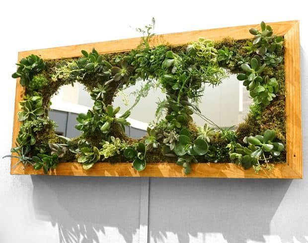 This vertical wall garden board features large circles cut out into the middle of it. This makes the board interesting to look at as well as highly functional as far as planting goes. If you're looking for a different design concept, this could be the next thing you decorate your patio garden area with. It's a great design and the plants look gorgeous in this setting.