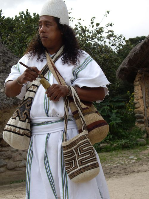 A typical Arhuaco man, any moment of the day: chewing, poporo-ing, and covered with bags