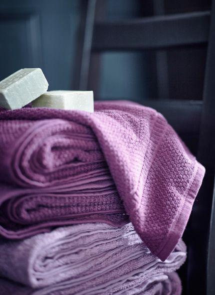 En hög med mörk- och ljuslila handdukar med några ljusgröna handgjorda tvålar ovanpå.
