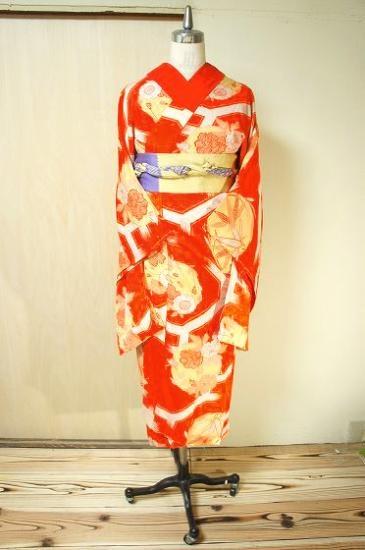 橙色に近い綺麗な朱色地に、大胆に染め出された笹や牡丹、桜の花丸文様で飾られた蜀江模様が美しい袷の縮緬長襦袢です。