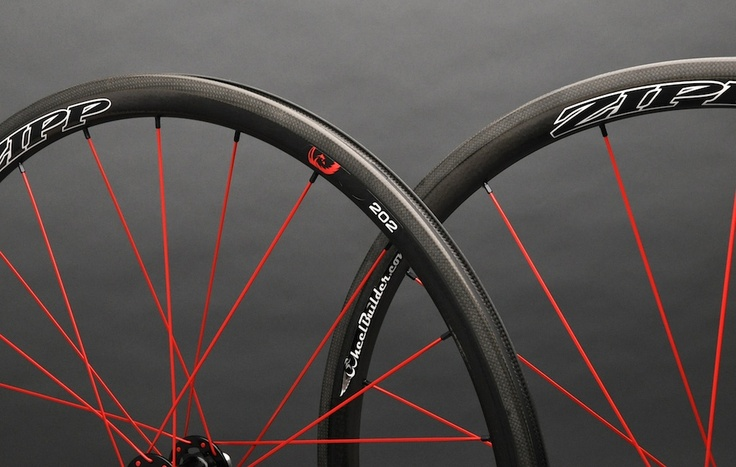 Precision handcrafted Zipp 202 Firecrest carbon clincher rims with black Chris King R45 hubs, red DT Swiss aerolite bladed spokes, and black Wheelbuilder.com high-strength alloy nipples. 1340g.