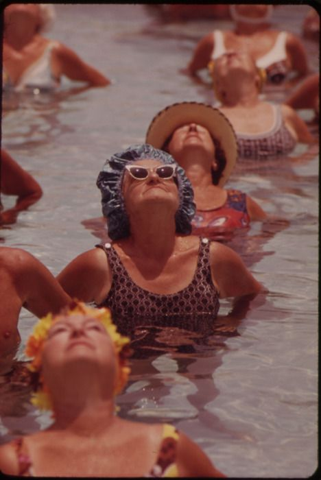 Residents take part in organized daily exercises in one of the public pools at century village retirement community, 1975.
