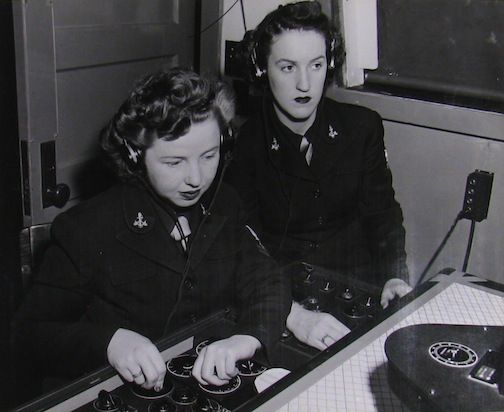 """In the Link trainer, the instructor sits at a desk while the """"pilot"""" goes into a flight simulator. In this photo from 1944, Hannah Barnes and Elizabeth Ripley practice the new desk techniques when using the new machine for celestial navigation during their 10-week training at NAS Seattle."""