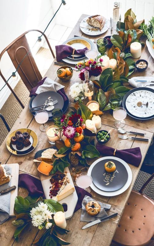 Fall inspired rustic table setting with deep purple napkins, an assortment of dinnerware and a gorgeous table-length floral arrangement of magnolia leaves, persimmons, dahlias and ranunculus.  Photography by: THE TURQUOISE HOME