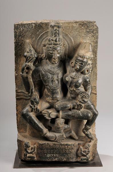 Le couple divin Vishnu Lakshmi assis en Lalitasana , tendrement enlacés , Vishnu coiffé d'une haute tiare Mukuta , sous une forme à quatre bras , tenant de sa main supérieure le bouton de lotus Padma , les deux mains inférieures l'une de portant la conque çAnka et l'autre tenant par la taille sa Shakti Lakshmi partiellement assise sur son genoux. Elle tient le disque çAkra . Le couple divin est figurés nus couverts de colliers, pectoraux et autres joyaux . Pierre noire . Inde . Bihar…