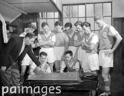 Bournemouth FC manager Freddie Cox (left) is seen in a council of war with his players in the dressing room at the Third Division club's ground in Bournemouth. Mr Cox and his men are planning tactics for their 5th round FA Cup tie against Tottenham Hotspur. 13th February 1957
