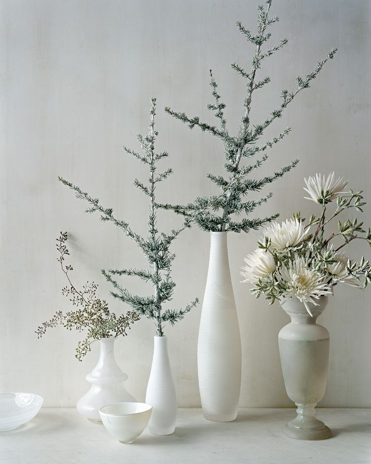 In place of a fussy centerpiece, arrange white vases and fill them with white spider mums, seeded eucalyptus, and blue Atlas cedar branches lightly frosted with silver floral spray paint. Line them up across a mantel, along a windowsill, or down the middle of a table.