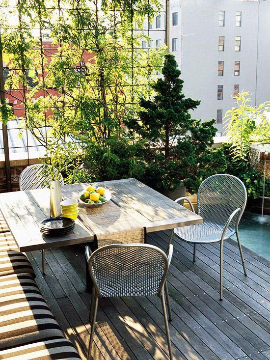"""Exemplo de espaço para refeições, com piso em deck de madeira, bancos típicos de """"canto alemão"""" mesa também em madeira, cadeiras em alumínio e lindo trabalho de paisagismo com trepadeiras, e espelho d´água."""