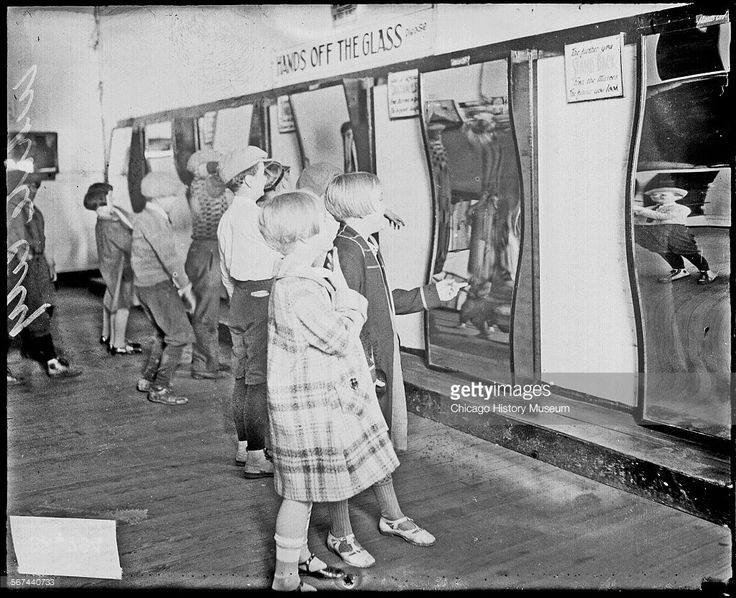 Informal full-length portrait of children standing in front of a display of trick mirrors at the White City amusement park, located at 63rd and South Parkway (King Drive) in the Englewood community area, Chicago, Illinois, 1927. From the Chicago Daily News collection.