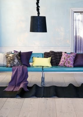 Bright blue vinyl couch with deep purple pillows beautifully grounded with black