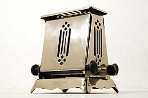 HOTPOINT  15032G2 (black 01)    early 1920s, Australia  Nickel plated metal, black bakelite  240 Volts/700 Watts    Hotpoint toasters were made by General Electric in the USA, in England and Australia. This one is from Australia. A solid made, big toaster with nice cutouts and big bakelite handles.