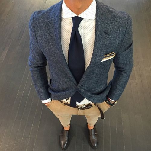 Stand out among other stylish civilians in a navy blazer and camel chinos. Dark brown leather double monks will add elegance to an otherwise simple look.   Shop this look on Lookastic: https://lookastic.com/men/looks/blazer-dress-shirt-chinos/17958   — White Polka Dot Dress Shirt  — Navy Tie  — Navy Blazer  — White Pocket Square  — Khaki Chinos  — Dark Brown Leather Double Monks