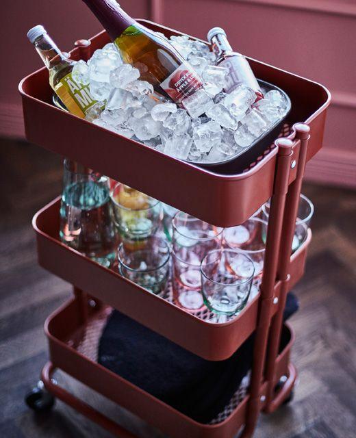 RÅSKOG Servierwagen in Rot/Braun wird hier als Bar genutzt. Darauf befinden sich Gläser, ein Behälter mit Eis, Servietten und Getränke.
