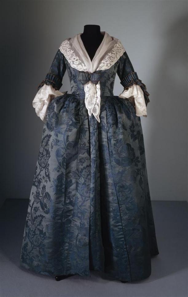 Robe ajustée, bestaande uit overkleed en tablier, van blauw zijden damast met groot ingeweven bloemtakpatroon | Modemuze