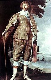 Long hair, Van Dyke beard and moustache. Falling collar,  doublet high waist, slashing only in the upper body area, baldric.  Venetians, stockings cuffed over bucket top boots. Note: high heels  for men. Gauntlet gloves, walking stick, plumed beaver hat.
