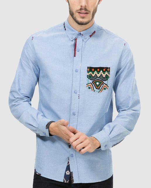 Camisa de manga larga, regular fit de color azul claro con detalles a contraste. Tiene el cuello americano, puños redondeados y un bolsillo estampado en el pecho.