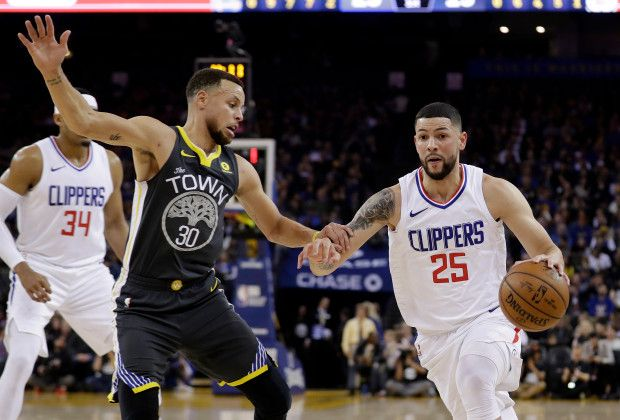 Los Angeles Clippers' Austin Rivers (25) dribbles next to Golden State Warriors' Stephen Curry (30) during the first half of an NBA basketball game Thursday, Feb. 22, 2018, in Oakland, Calif. (AP Photo/Marcio Jose Sanchez)