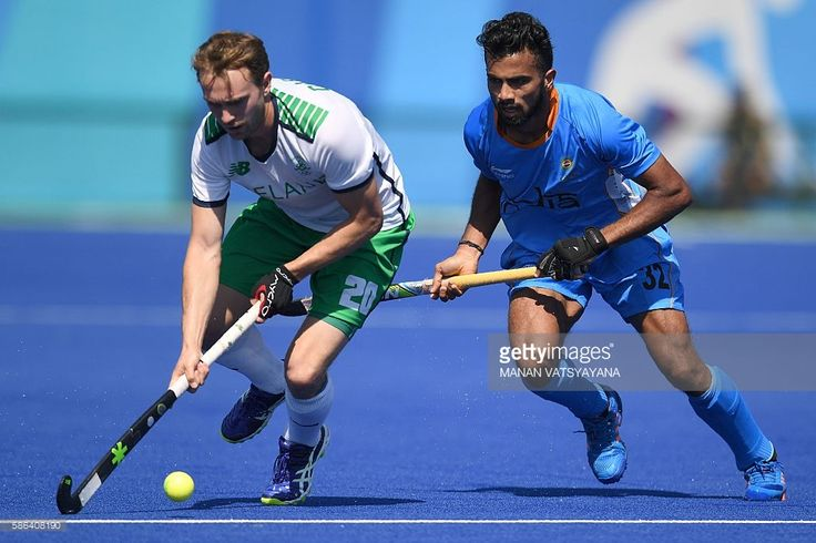 India's Chandanda Thimmaiah (R) and Ireland's Michael Darling fight for the ball during the men's field hockey India vs Ireland match of the Rio 2016 Olympics Games at the Olympic Hockey Centre in Rio de Janeiro on August, 6 2016. / AFP / MANAN