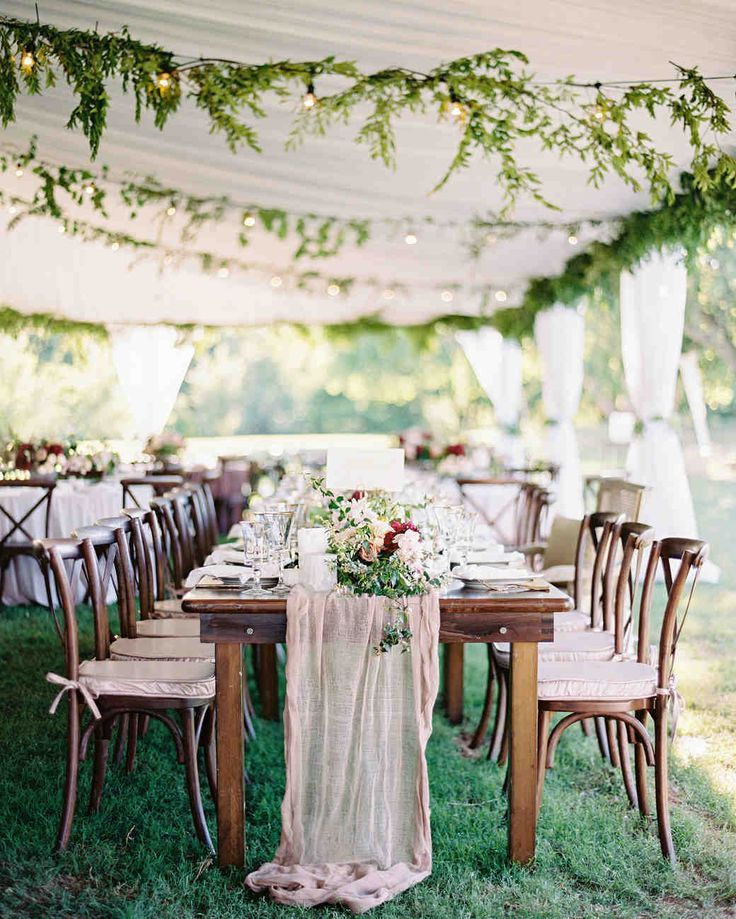 A Romantic, Flower-Filled Wedding in Oklahoma | Martha Stewart Weddings - It was straight to the tent for the reception following the ceremony. The drapery and garlands of greenery soften the tent, and the round tables were dressed with mauve velvet cloths. Here, the head table, was dressed with a gauzy runner. Low arrangements of roses, scabiosa, and greenery added more color to the space.