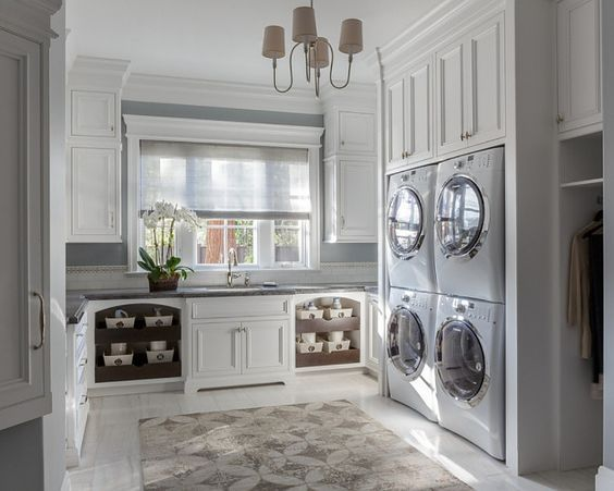 Laundry room with with stacked double washer and dryer, laundry chute and floor to ceiling cabinets