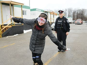 Barrie Advance reporter stumbles through sobriety test - Barrie Advance reporter Sara Carson tries to walk in an impairment suit under the watchful eye of Barrie Police Sgt. Glen Furlong.