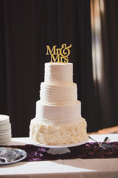 four tier wedding cake with different frosting designs gold cake topper meysenburg photography