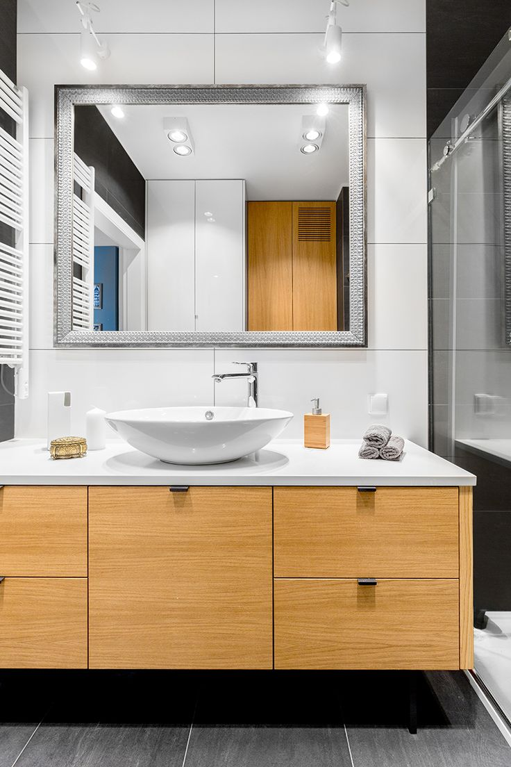 Bathroom black & white with natural wood cupboard.