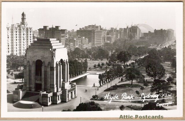 Vintage real photo postcard of Hyde Park in Sydney, New South Wales, Australia. Shows the ANZAC War Memorial, Lake of Reflections and the Sydney Harbour Bridge in the distance behind buildings and cranes. A Mowbray 'Scenic and Historic Views' postcard.