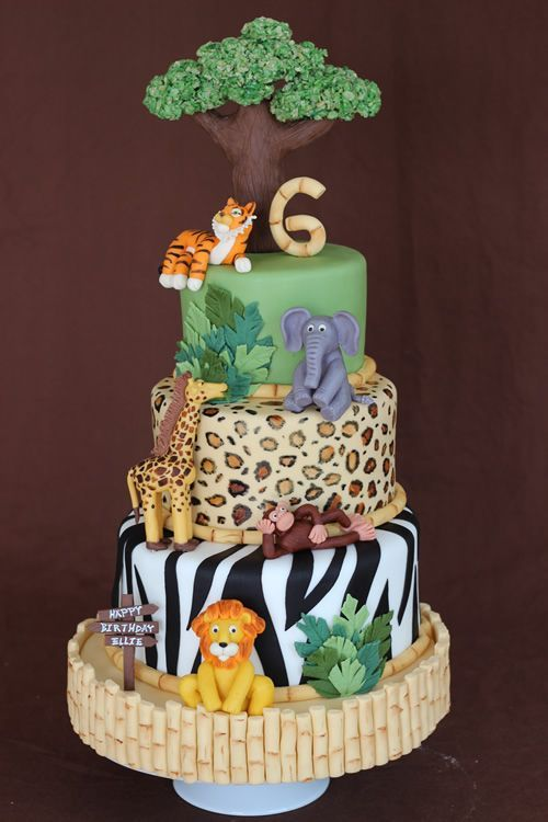 A jungle safari cake with chocolate animals and animal print on the inside as well as the outside.
