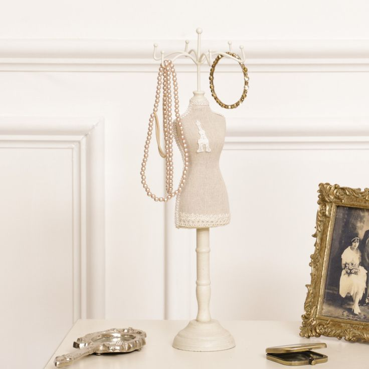 A Parisian themed bridal lace jewellery stand complete with six hooks to the top for safely hanging necklaces and bracelets. A good sized item that is suitable for hanging long or short pieces of jewellery, decorated with a small Eiffel tower embroidery attachment to the bodice. Wooden standing frame decorated in distressed beige, suitable for all surface types complete with decorative lace attachment to the outline of the bodice A vintage themed gift idea for any ladies dressing table!