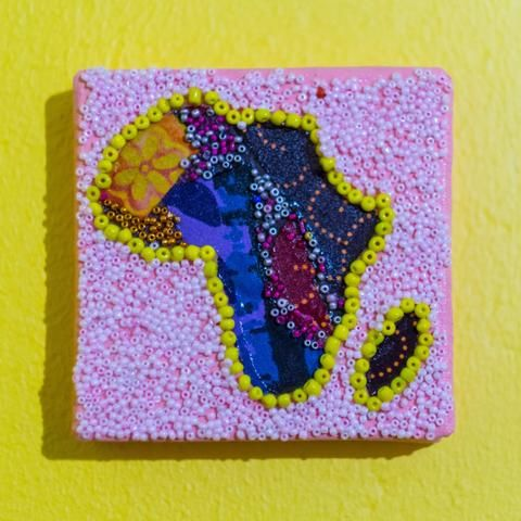 Shop: Canvas D'Afrique - Pink Flower. This Africa is partially beaded on canvas in light pink and yellow with a center of a fabric collage. Size: 10cm x 10cm. By Beadoir D'Afrique