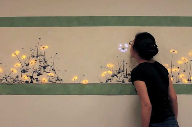 An artist from the MIT Media Lab has created an interactive painting of a dandelion field, where viewers can blow on the seeds and watch the glowing sparks fly, fall and give life to new flowers.    Jie Qi, a doctoral student at the lab's High-Low Tech group and graduate in mechanical engineering, intersperses electronic design with paper and textiles to create novel concepts like Pu Gong Ying Tu (translated as Dandelion Painting).