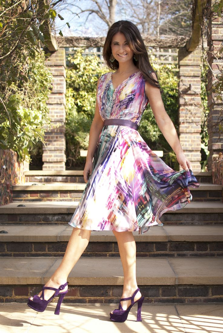 Summer party! Sara Brett Design Director at Bernshaw wears a multi colours rainbow dress with purple sandals. The dress has a art inspired paint brush effect in bright colours from yellow, purple and pink. Wear this dress to a summer wedding, the races, a prom or the polo https://www.bernshaw.com/party-evening-cocktail-dresses-fashion-designer-blog/item/311-blog-ss15-trend-colour-pop