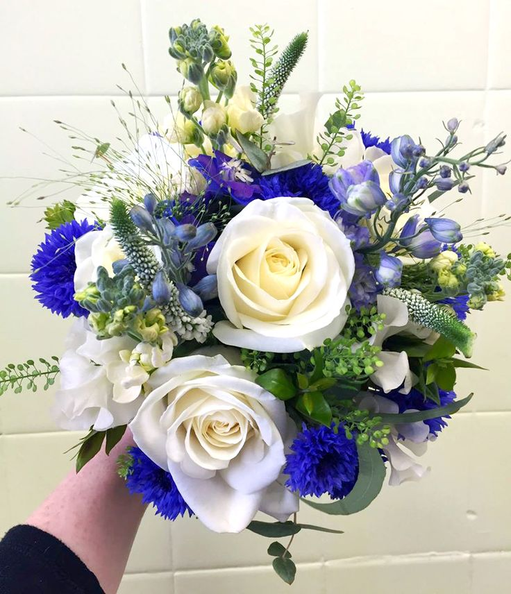 Gorgeous blue and cream themed wedding. Bridal bouquet created by our Head Florist Charlotte King. We love the striking electric blue accents in this round style bouquet. http://www.isleofwightflowers.co.uk/