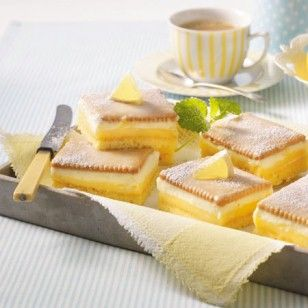 Saftiger Rührteig, cremiger Pudding, Schlagsahne und knackige Butterkekse - die fruchtigen Zitronenschnitten sind der Hit. Wir zeigen, wie der Blechkuchen gelingt.