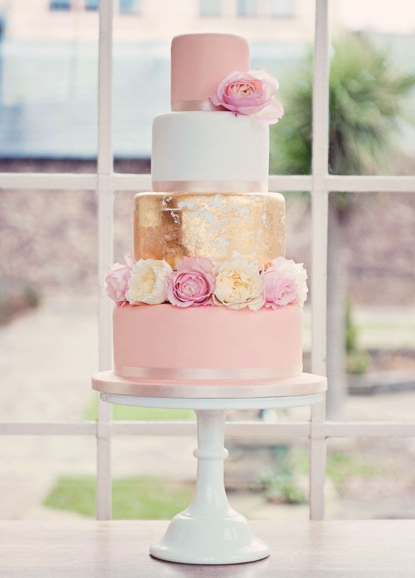 10 Wedding Cakes We Love For Summer: This chic pink and gold cake radiate that summer shine. Fluffy blooms add a touch of romance to the sweet confection.