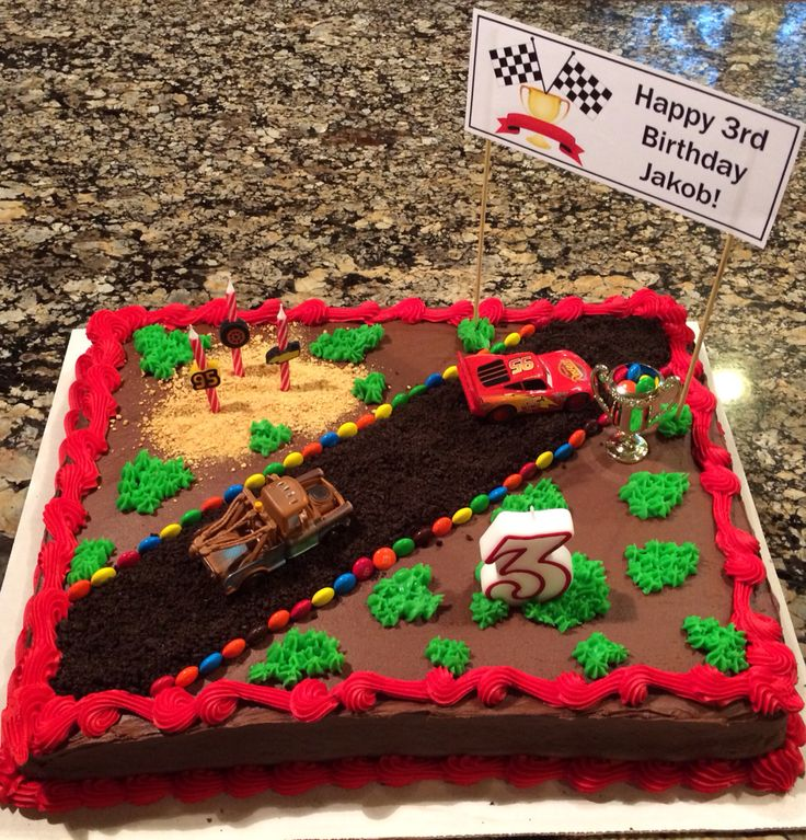 Disney Cars/Lightning McQueen birthday cake  This is a Costco cake decorated (by their bakery) with chocolate icing and a red border only. The track is made from oreo crumbs with an M&M border. The sand is made from graham cracker crumbs. I bought green pre-made frosting with a piping tip from the grocery store to make the grass. I designed a sign and attached it with wooden skewers to hold the birthday banner. Super easy cake!